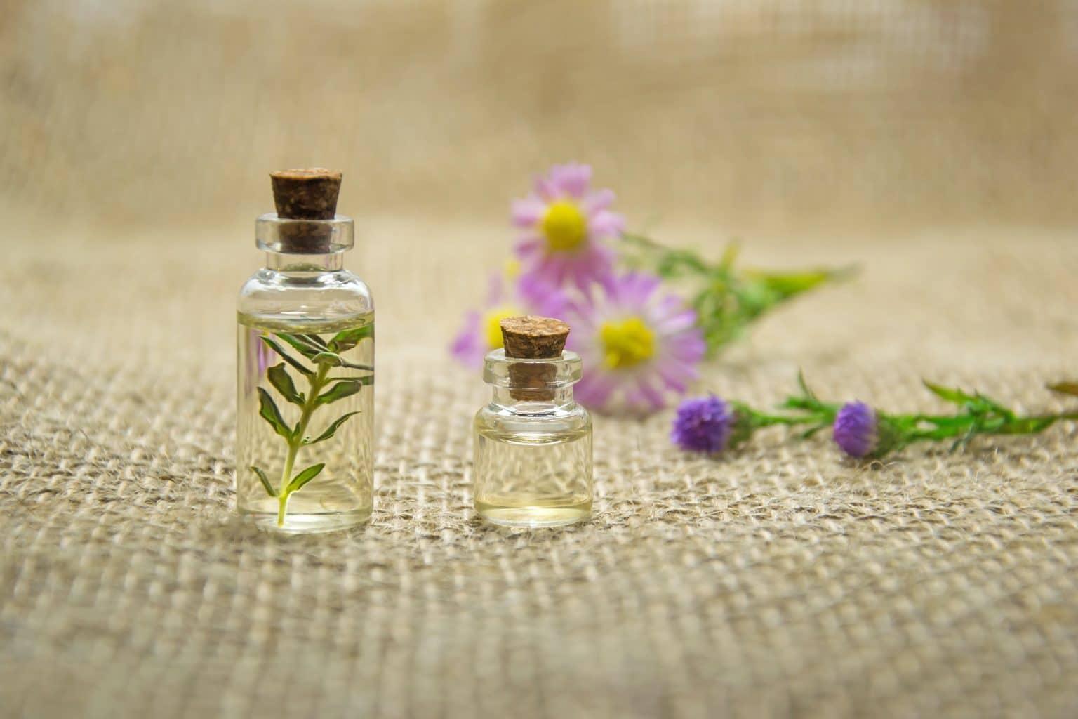 Ätherisches Öl in kleiner Flasche mit Korken und Blumen auf Jute