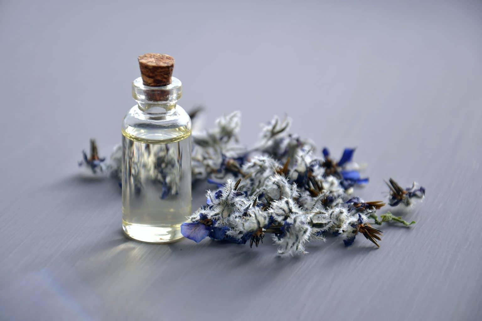 Ätherisches Öl in Glasflasche mit Kräutern