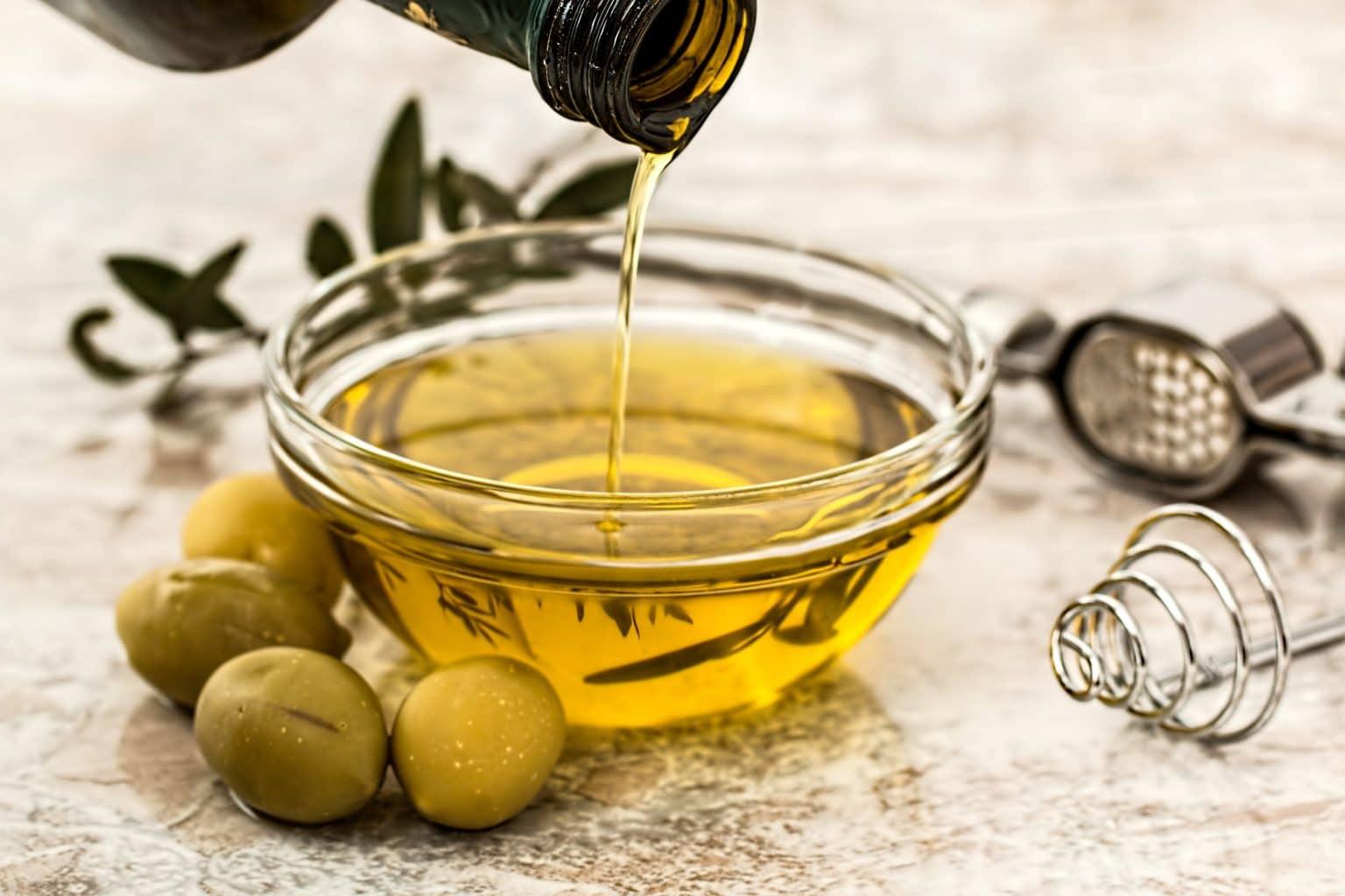 Olivenöl aus Flasche in eine Glasschale mit Oliven und Kräutern und Knoblauchpresse