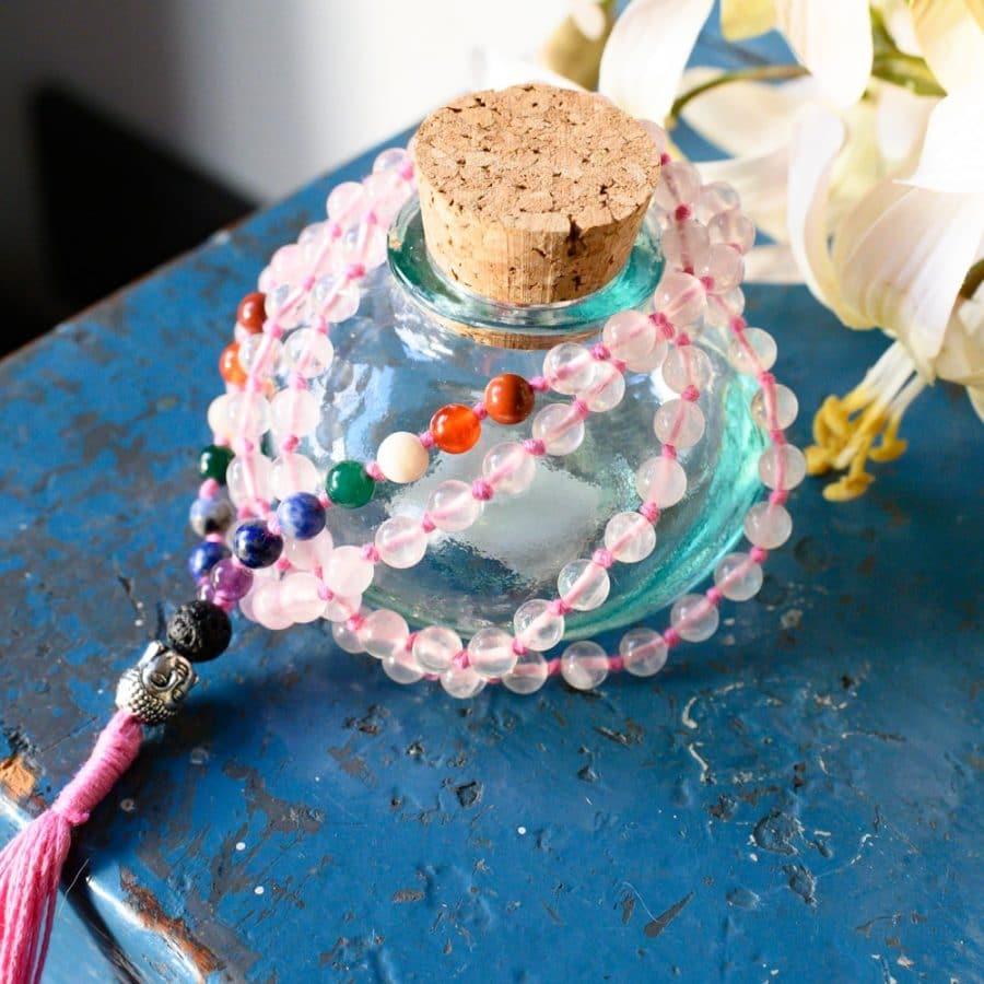 Glasflasche Mala Kette bunt auf blauem Schrank mit Blumen