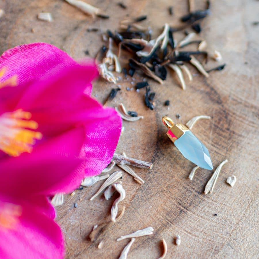 Halschakra Edelstein Anhänger Amazonit auf Holz mit Blume