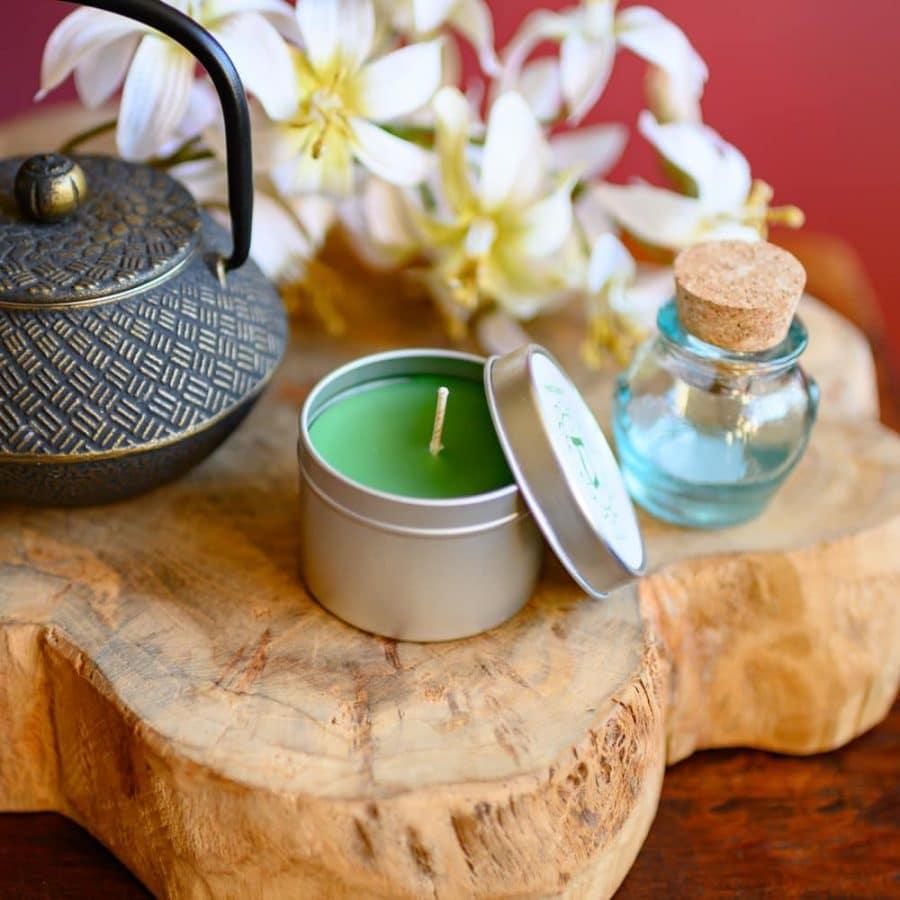 Chakra Kerze Grün mit teepott und Glasfläschchen auf Holz mit weißen Blumen