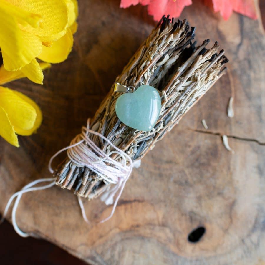 grüner aventurin herzanhänger auf slabei auf Holz mit gelber Blume