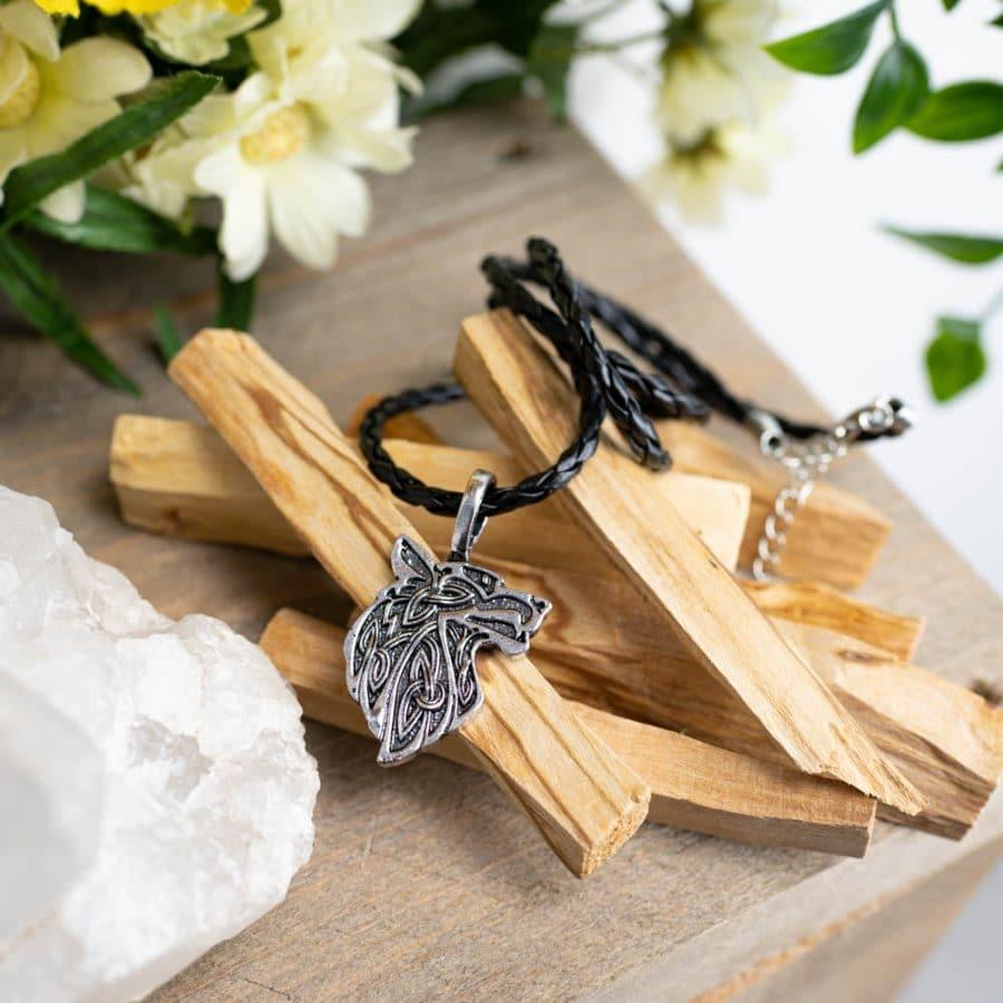 amulett Wolfskopf an schwarzer Waxhskordel auf Palo Santo mit Blumen und Kristall