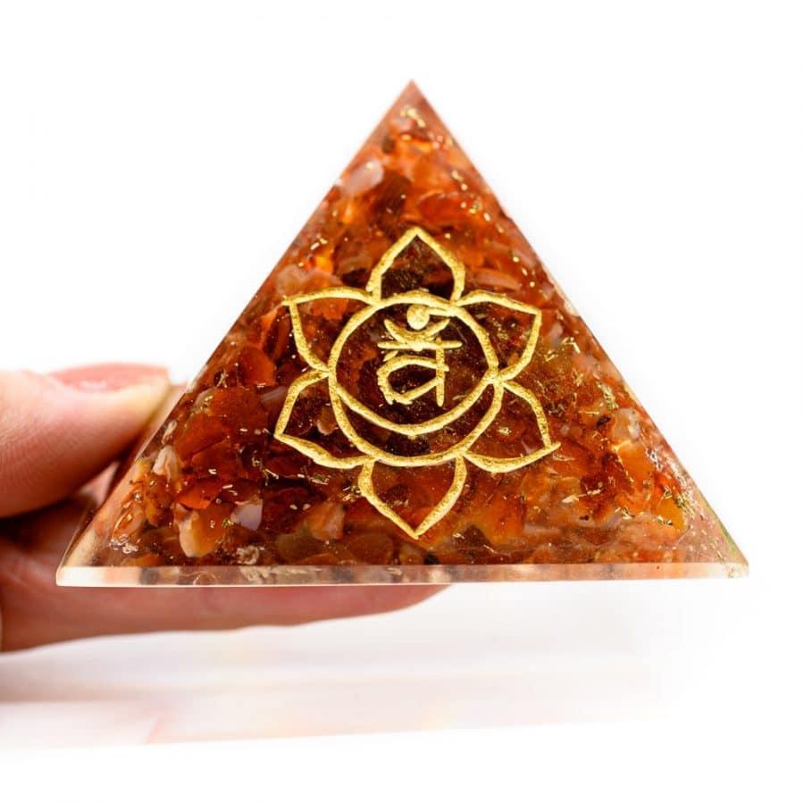 2. chakra pyramide rot symbol gold in hand vor weißem hintergrund