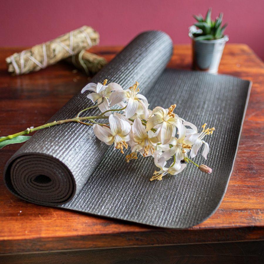 schwarze Yogamatte mit Blumen auf Holz