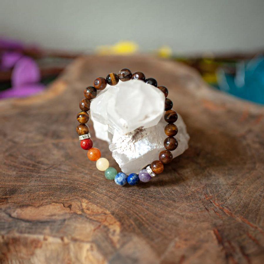 Perlenarmnband chakra farben auf holz mit Kristall