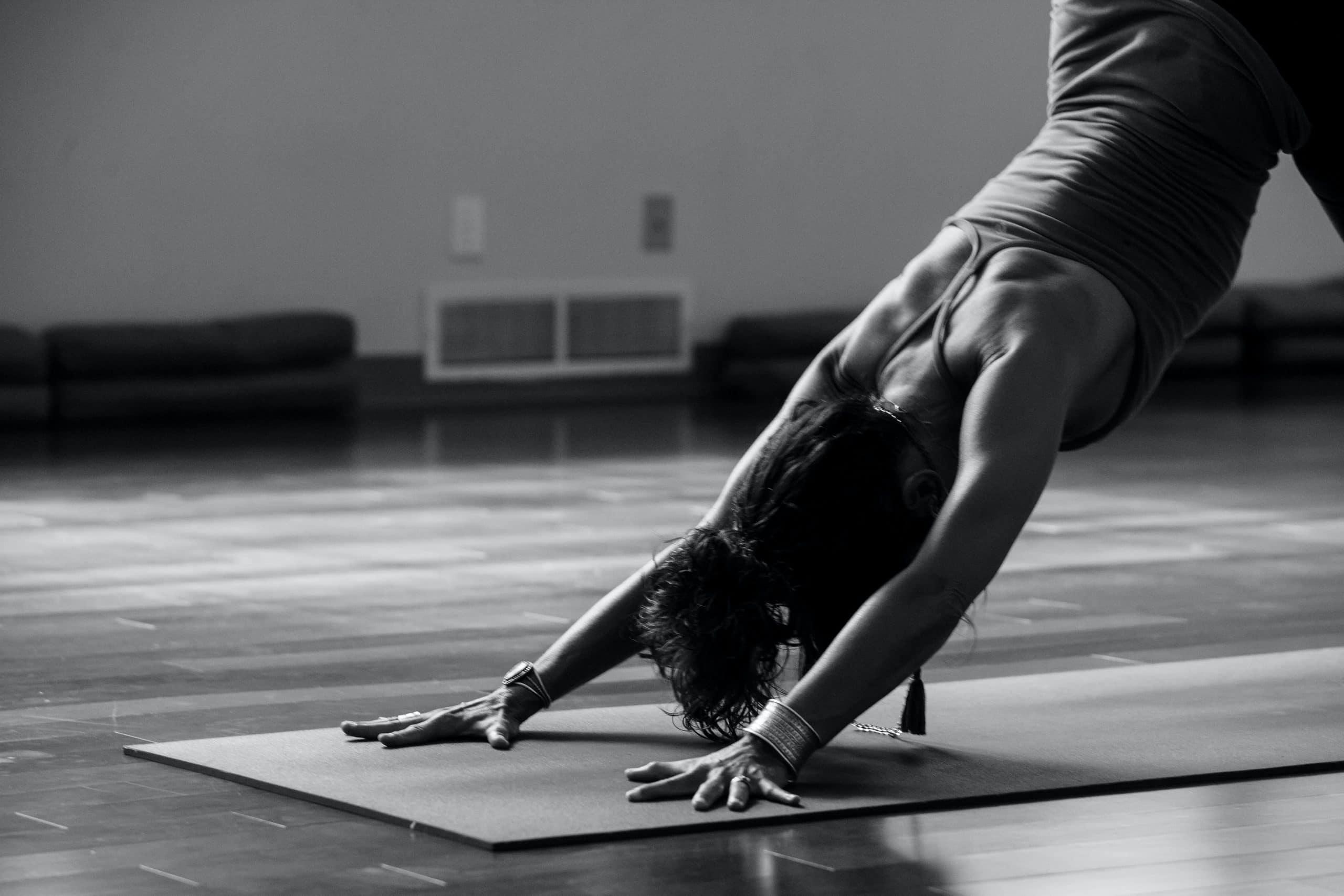Frau schwarz weiß Yoga Pose auf Matte in Studio