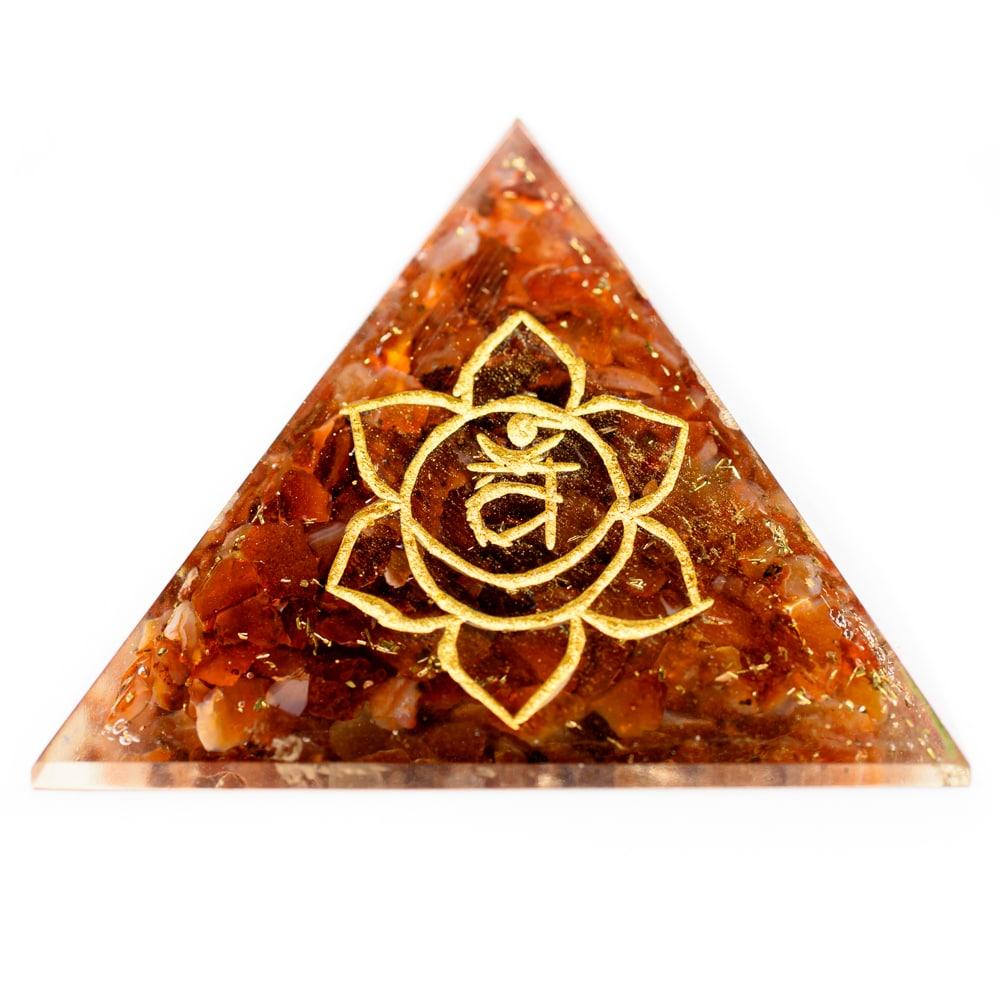 orange edelsteine orgonit pyramide mit chakra zeichen gold auf weißem hintergrund